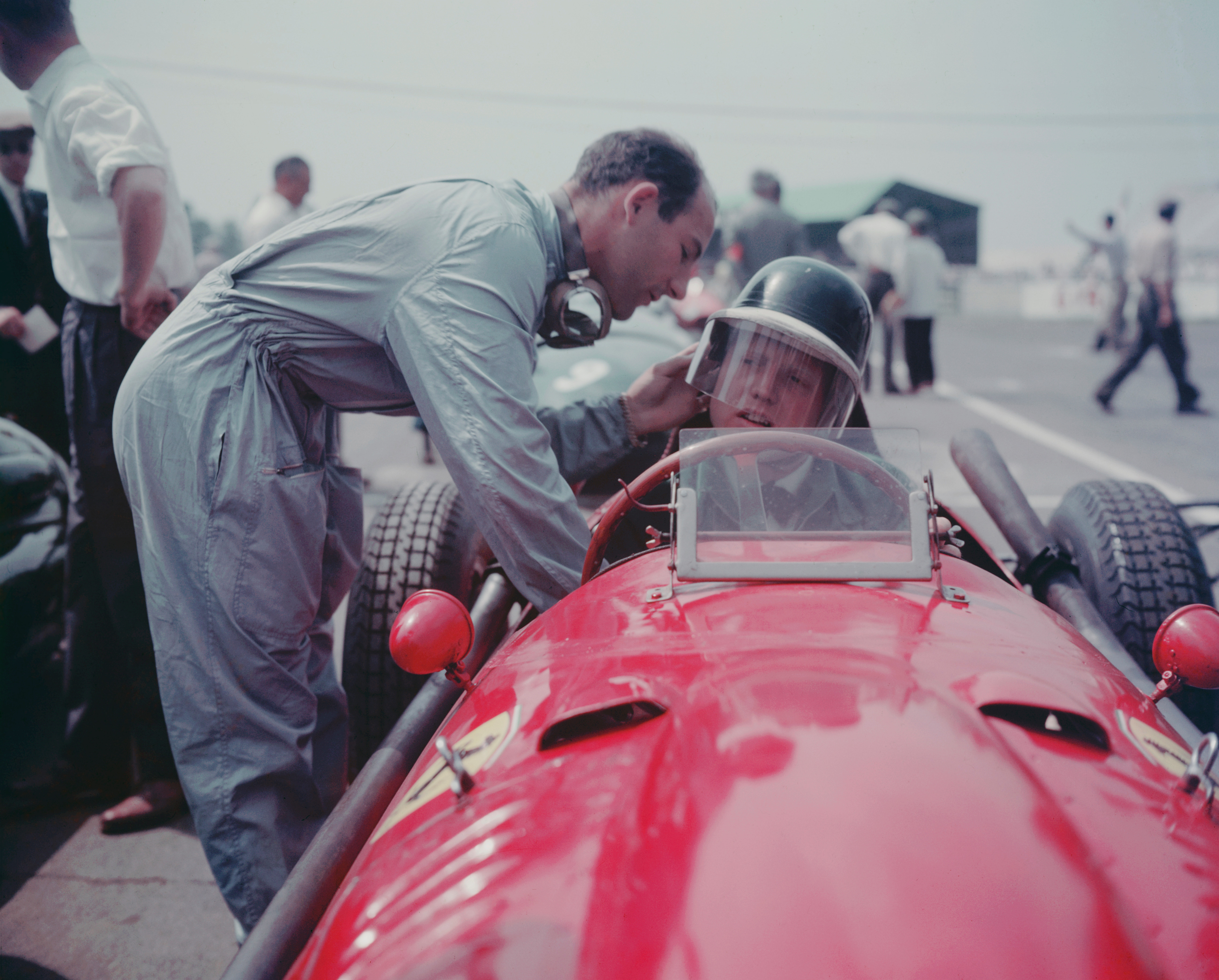 British racing icon Stirling Moss (left) adjusts the helmet of Ferrari driver Mike Hawthorn before a race in 1958